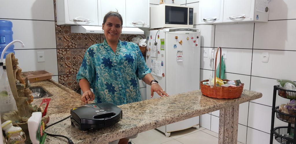 A imagem mostra Marcelle a frente do balcão da sua cozinha americana: ela cuida sozinha da sua casa e da sua própria vida.