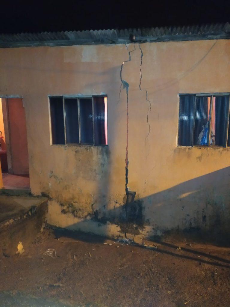 parede de casa com duas janelas e diversas rachaduras